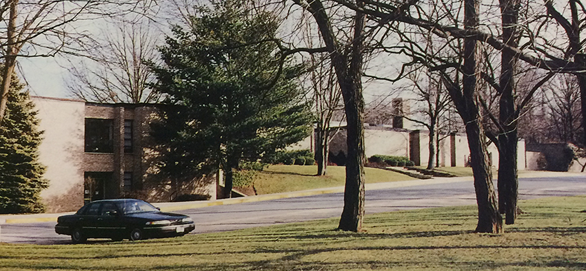 Color photograph of Wolftrap Elementary School taken in 1998 from the same angle as the 1968 photograph. A single car, a blue Ford four-door sedan, is parked in front of the building. The trees are considerably larger, but the building looks relatively the same except for an addition to the structure on the far right of the photograph.